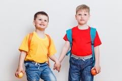 在T恤杉和牛仔裤的愉快的孩子有在白色背景的背包的 免版税库存图片