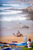 在Taghazout海浪村庄,摩洛哥2附近供以人员和他的骆驼 免版税图库摄影
