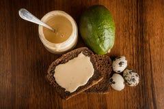 在tahini的顶视图在瓶子,黑麦面包,鲕梨,三个鹌鹑蛋 库存图片