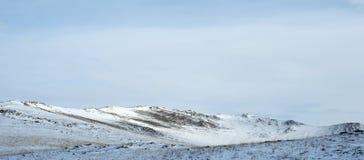 在Tazheran干草原的清早日出 积雪的小山在紫外树荫下被上色  免版税库存照片