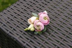 在tenderless钮扣眼上插的花,特写镜头的桃红色毛茛属和玫瑰芽 库存照片