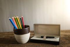 在thegray杯子的葡萄酒蜡笔有在木地板上的笔箱子的 库存图片