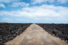 在Timanfaya国家公园跟踪在熔岩中岩石的路在兰萨罗特岛,加那利群岛西班牙 库存照片
