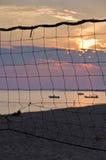 在Toroni海滩的日落通过老排球网在Sithonia 免版税库存照片