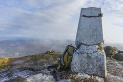 在trig点旁边的黄色背包在一座山的上面在苏格兰,在地面上的雪 免版税库存照片