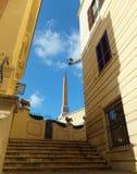在Trinita dei Monti教会前面的方尖碑在罗马,意大利,观看从一个狭窄的楼梯台阶它 免版税图库摄影
