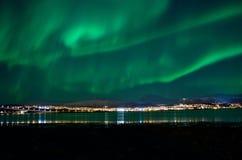 在tromso城市海岛、海湾和多雪的山的极光borealis 库存图片