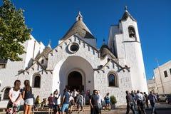 在Trullo教会前面的游人在阿尔贝罗贝洛 库存图片