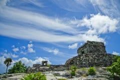在Tulum一个古老石塔上升在与坚定到左边的曲拱的一个土墩顶部在蓝天下 免版税库存图片