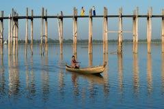 在Ubein桥梁的晚上 Burmanese在湖Tauntome的一条传统木小船游泳 图库摄影