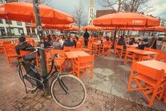 在unbrellas下的人谈的和饮用的啤酒与地方啤酒厂商标De Koninck 免版税库存照片