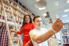 在univercity图书馆里结合学生,看书,准备对检查,获得乐趣,做selfie 免版税库存图片