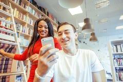 在univercity图书馆里结合学生,看书,准备对检查,获得乐趣,做selfie 免版税库存照片