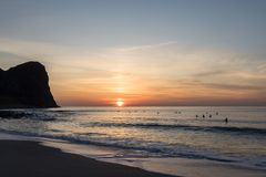 在Unstad海滩的美好的日落 冲浪者在水中在背景中 库存图片