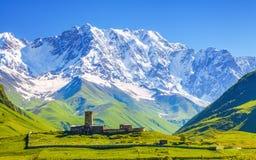 在Ushguli村庄的看法积雪覆盖的Mt的脚的 什哈拉山 库存照片