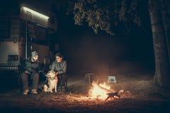 在vacantion的夫妇在营火附近 库存图片