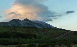 在Vilyuchinsky stratovolcano上的双突透镜的云彩在黎明 从brookvalley Spokoyny的看法在外面北部的脚 免版税库存照片