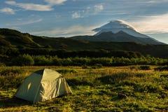 在Vilyuchinsky stratovolcano背景的旅游帐篷在黎明 从brookvalley Spokoyny的看法在脚外面 免版税图库摄影