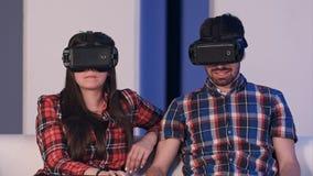 在vr耳机观看的电影的年轻夫妇坐沙发 免版税库存照片
