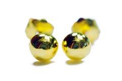 在w在球形形状的金下垂有浮雕的贝壳耳环首饰隔绝的 免版税库存图片