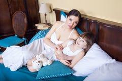 在wak以后的早晨照顾和她逗人喜爱的女儿谎言在床上 免版税库存图片