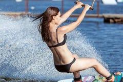 在wakeboarding的妇女骑马 免版税库存照片
