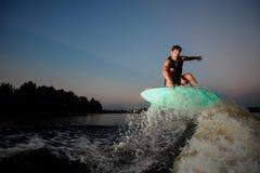 在wakesurf的有吸引力的人骑马在日落期间的河下 库存图片