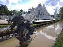 在Wat荣Khun,白色寺庙附近的龙雕象在清莱府,泰国 免版税图库摄影
