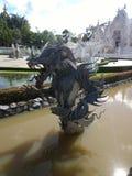 在Wat荣Khun,白色寺庙附近的龙雕象在清莱府,泰国 库存图片