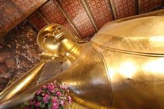 在wat pho的斜倚的菩萨金雕象面孔在曼谷 库存图片