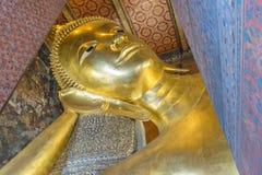 在Wat Pho,曼谷,泰国的斜倚的菩萨金雕象面孔 库存图片