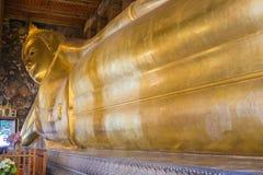 在Wat Pho,曼谷,泰国的斜倚的菩萨金雕象面孔 库存照片