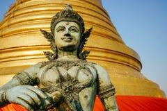 在Wat Saket寺庙一大金黄stupa的背景的泰国雕塑在曼谷 库存照片
