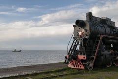 在waterlandscape背景的减速火箭的机车 图库摄影