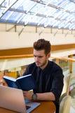 在webinar期间的有胡子的男性经理藏品笔记薄在netbook,坐在办公室内部 免版税库存图片