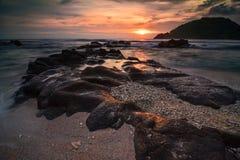 在Wediombo海滩的日落与珊瑚海滩 图库摄影