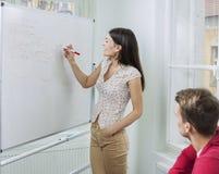 在whiteboard的女实业家文字在会议 免版税库存照片
