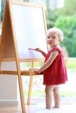 在whiteboard的小女孩图画 免版税库存图片