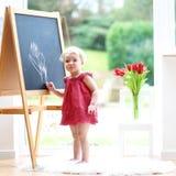 在whiteboard的小女孩图画 免版税图库摄影