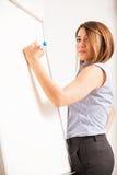 在whiteboard的逗人喜爱的女性家庭教师文字 免版税库存图片
