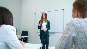 在whiteboard附近的年轻微笑的女老师教练高中生的在学院教室 股票视频
