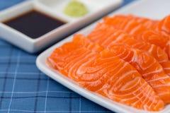 在whiteJapanese传统盘的三文鱼未加工的生鱼片在蓝色选项 免版税库存图片