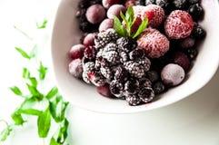 在whitw正方形板材的冷冻莓果有束的在白色的薄菏 免版税图库摄影