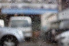 在Windows的雨下落在车库前面 免版税图库摄影