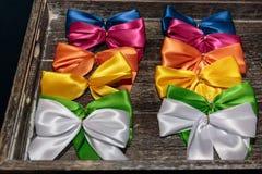 在Wodden箱子的五颜六色的礼物丝带弓 图库摄影