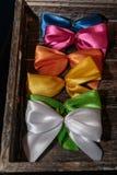 在Wodden箱子的五颜六色的礼物丝带弓 库存照片