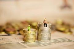 在women's和men's收入之间的区别或与微型剪影的薪金概念在堆硬币 库存照片