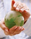 在women&#39的绿色行星; s手 免版税库存照片