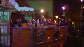 在Xmas假期期间,快乐的人民坐在圈子的小孩子的火车 影视素材