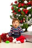 在Xmas树前面的好奇婴孩 免版税库存图片